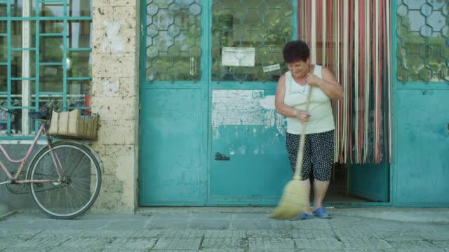 Medium shot of woman sweeping sidewalk in front of store / Asenovtsi, Bulgaria