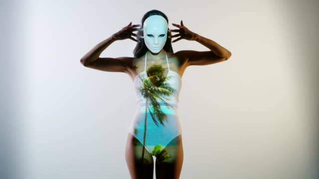 stockvideo's en b-roll-footage met medium shot of woman wearing mask dancing and daydreaming about beach / cedar hills, utah, united states - digitaal samengesteld beeld