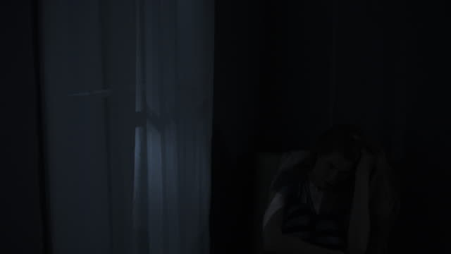 medium shot of woman with insomnia sitting in chair at night / cedar hills, utah, united states - 精神障害点の映像素材/bロール