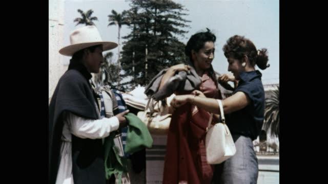 medium shot of women buying shawl on street - shawl stock videos & royalty-free footage