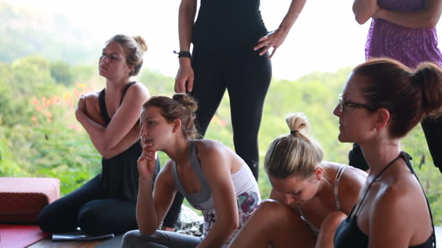 medium shot of women dressed in yoga attire, listening, looking camera left with some women standing in the background - kelly mason videos stock videos & royalty-free footage
