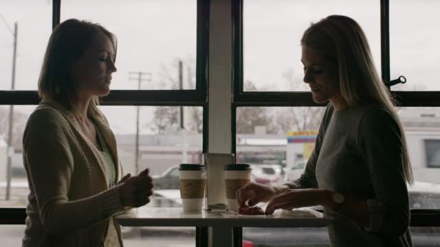 medium shot of women eating cookie at table near window / salt lake city, utah, united states - in movimento video stock e b–roll
