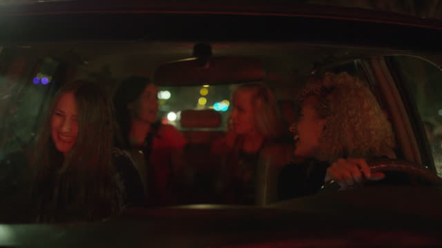 Medium shot of women singing to music in car behind windshield / Provo, Utah, United States