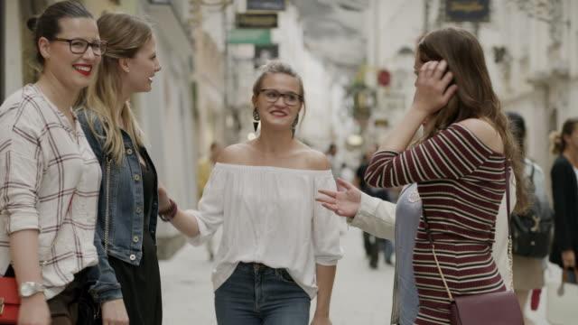 vídeos de stock, filmes e b-roll de medium shot of women talking and laughing in city / salzburg, austria - jaqueta jeans