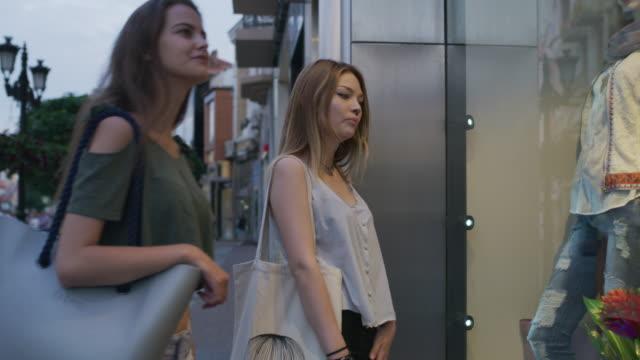 medium shot of women window shopping in city / plovdiv, bulgaria - schaufenster stock-videos und b-roll-filmmaterial