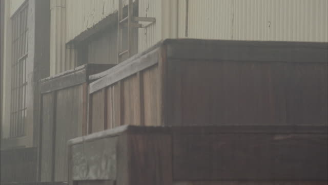 Medium shot of wooden crates on the outside of a warehouse on a rainy day.