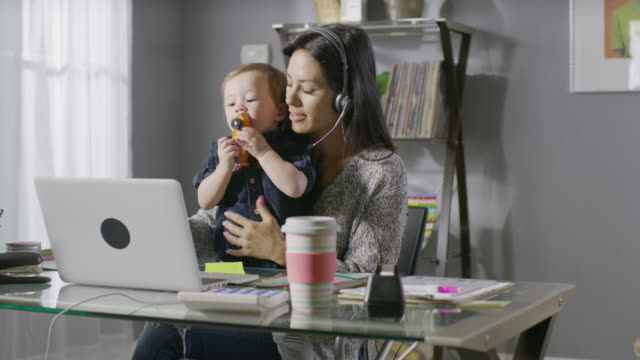 medium shot of working mother talking on headset distracted by son in lap / cedar hills, utah, united states - berufstätige mutter stock-videos und b-roll-filmmaterial