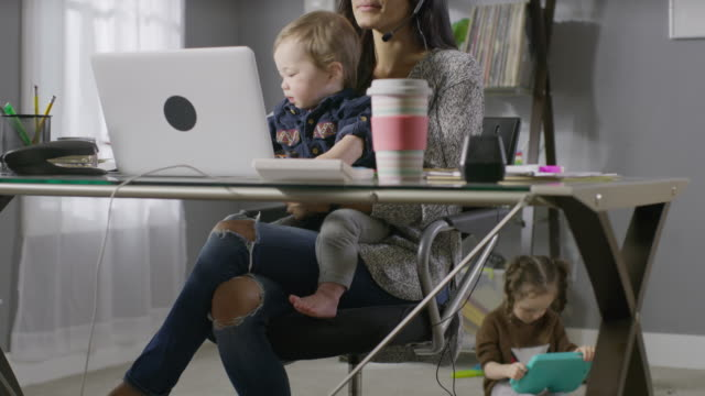 Medium shot of working mother talking on headset distracted by son in lap / Cedar Hills, Utah, United States