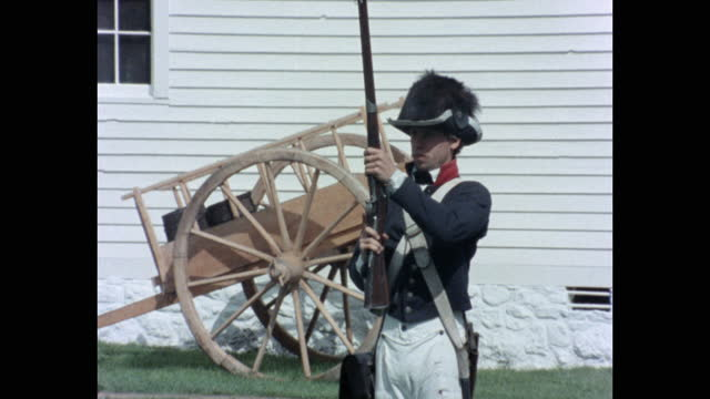 stockvideo's en b-roll-footage met medium shot of young army soldier loading and firing his musket while standing outdoors, michigan, usa - driekwartlengte