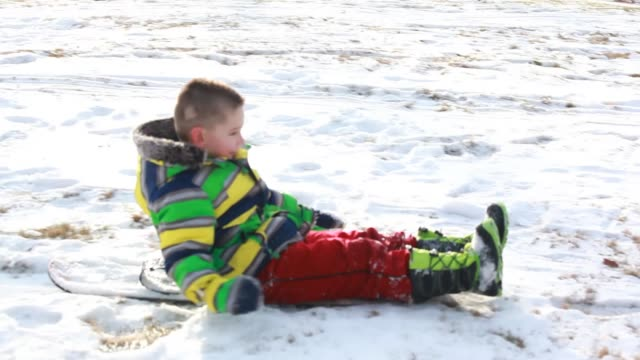 vidéos et rushes de medium shot of young boy scooting down a snowy hill while sitting on his snowboard - kelly mason videos