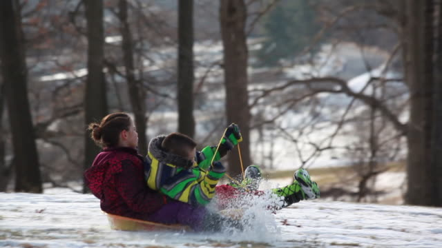 vídeos de stock e filmes b-roll de medium shot of young boy stealing sled down a snowy hill with young girl on the back - kelly mason videos