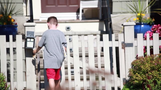 vídeos de stock e filmes b-roll de medium shot of young boy trying to open white picket fence gate to deliver newspapers - kelly mason videos