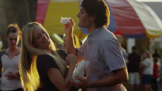 medium shot of young couple feeding each other cotton candy at carnival / american fork, utah, united states - teasing stock videos & royalty-free footage