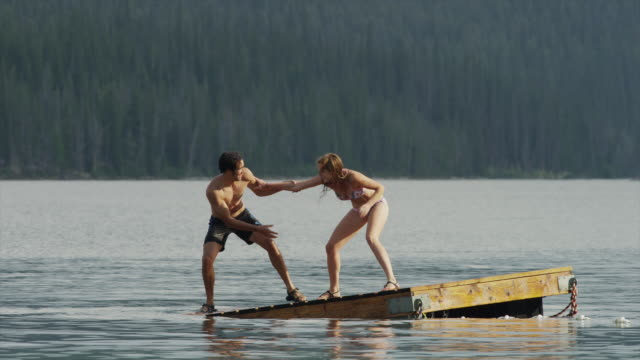 Medium shot of young couple playing on floating dock on lake / Redfish Lake, Idaho, United States
