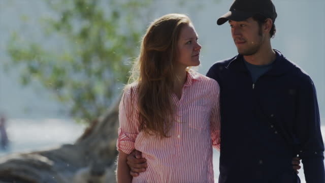 medium shot of young couple walking at lakeside / redfish lake, idaho, united states - baseballmütze stock-videos und b-roll-filmmaterial