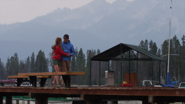 medium shot of young couple walking on dock over lake / redfish lake, idaho, united states - baseballmütze stock-videos und b-roll-filmmaterial