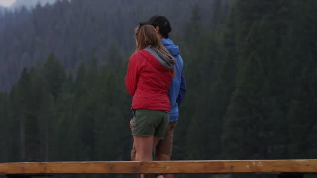 Medium shot of young couple walking on dock / Redfish Lake, Idaho, United States