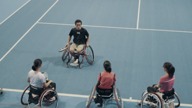 medium shot of young female wheelchair tennis players practicing together with their coach - endurance stock videos & royalty-free footage