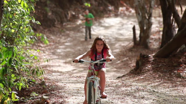 medium shot of young girl riding bike towards camera down a long windy country road and young boy runs after her. - kelly mason videos stock videos & royalty-free footage