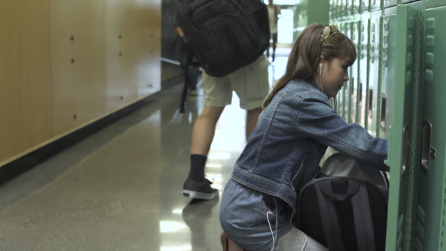 medium shot of young school girl packing into locker - 取り除く点の映像素材/bロール
