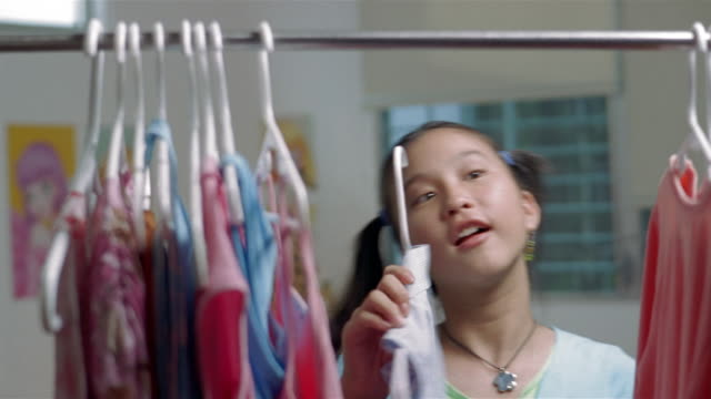 vídeos de stock e filmes b-roll de medium shot of young teenage girl looking through clothes in closet / picking out shirt - remover