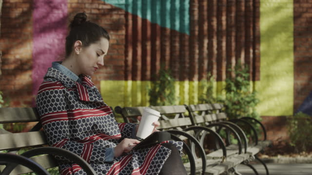 Medium shot of young woman drinking coffee and using digital tablet on urban bench / New York City, New York, United States