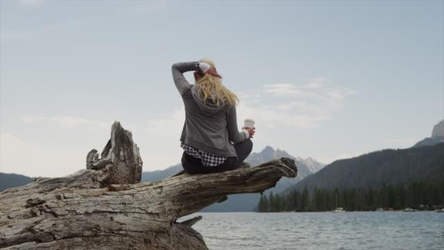 Medium shot of young woman drinking coffee on log at lake / Redfish Lake, Idaho, United States