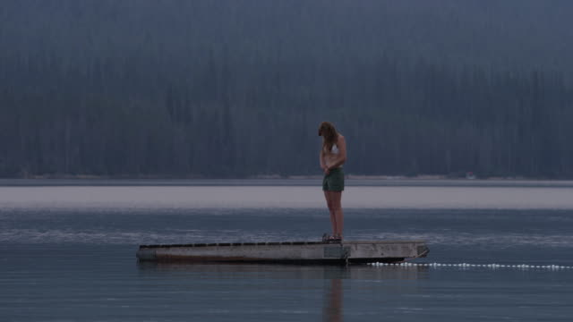Medium shot of young woman undressing and jumping from floating dock into lake / Redfish Lake, Idaho, United States
