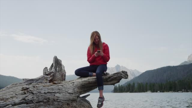 medium shot of young woman using cell phone on log at lake / redfish lake, idaho, united states - remote location phone stock videos & royalty-free footage
