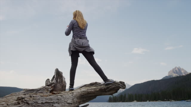 Medium shot of young woman videoing lake and mountains with cell phone / Redfish Lake, Idaho, United States