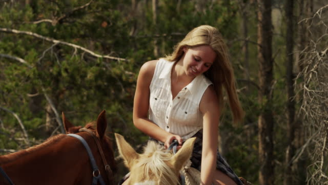 medium shot of young women horseback riding / idaho, united states - pferderitt stock-videos und b-roll-filmmaterial