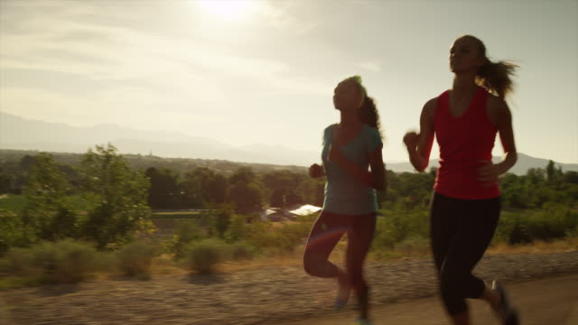 Medium shot of young women running on sunny road / Cedar Hills, Utah, United States