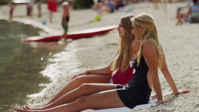 Medium shot of young women sitting on beach at lake / Redfish Lake, Idaho, United States