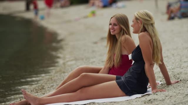 medium shot of young women sitting on beach at lake / redfish lake, idaho, united states - blondes haar stock-videos und b-roll-filmmaterial