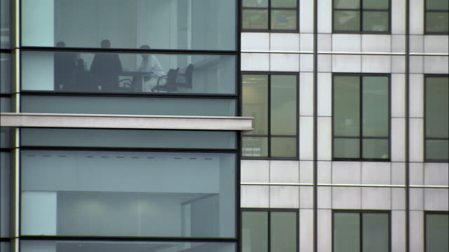 medium shot office building exterior with people in conference room/ london - verdecktes gesicht stock-videos und b-roll-filmmaterial