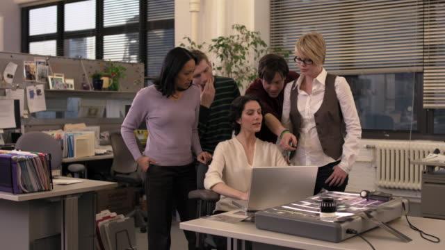 vídeos de stock, filmes e b-roll de medium shot office staff looking at laptop over manager's shoulder - mãos cobrindo boca
