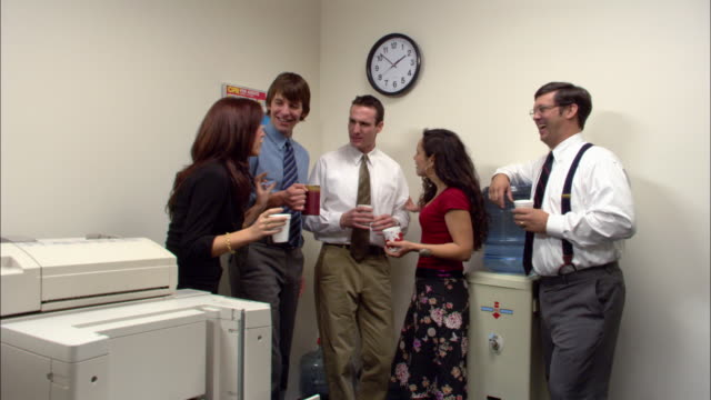 medium shot office workers holding drinks, gossiping and laughing by water cooler / los angeles - water cooler stock videos & royalty-free footage