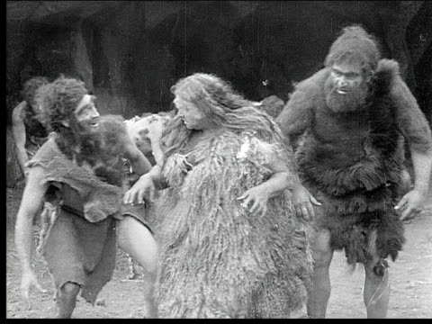 1914 B/W Medium shot Old cavewoman talking to group of cavemen in cave