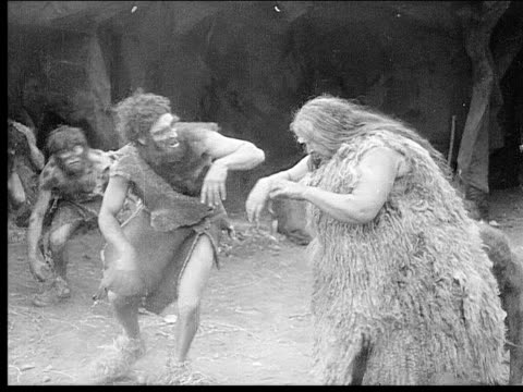 1914 b/w medium shot old cavewoman talking to group of cavemen in cave - evolution stock-videos und b-roll-filmmaterial
