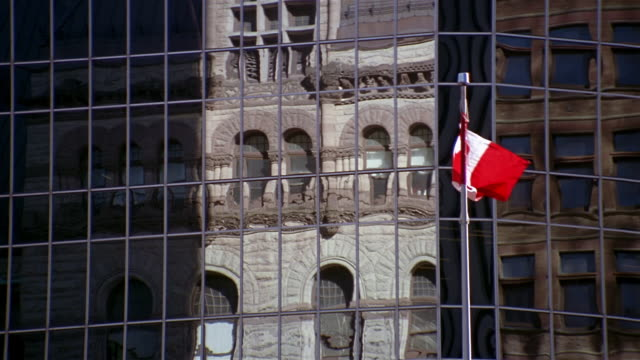 medium shot old city hall reflected on glass exterior of office building with canadian flag in front / toronto - kelly mason videos bildbanksvideor och videomaterial från bakom kulisserna