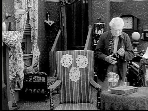 1913 b/w medium shot old man pouring glass of whiskey in living room / usa  - 1913 stock-videos und b-roll-filmmaterial