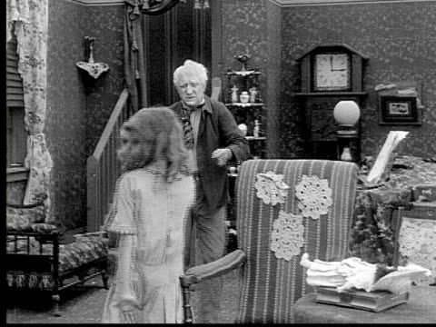 1913 b/w medium shot old man sneaking drink from grandfather clock while girl warns him before woman enters room / usa  - 1913 stock-videos und b-roll-filmmaterial