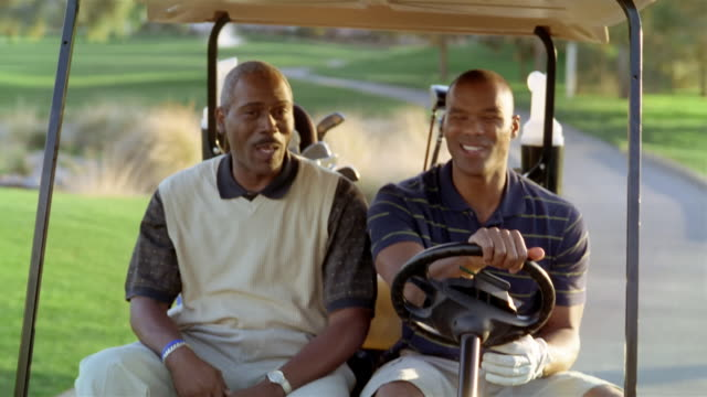 medium shot older man and younger man riding in golf cart on golf course and talking - golf cart stock videos & royalty-free footage