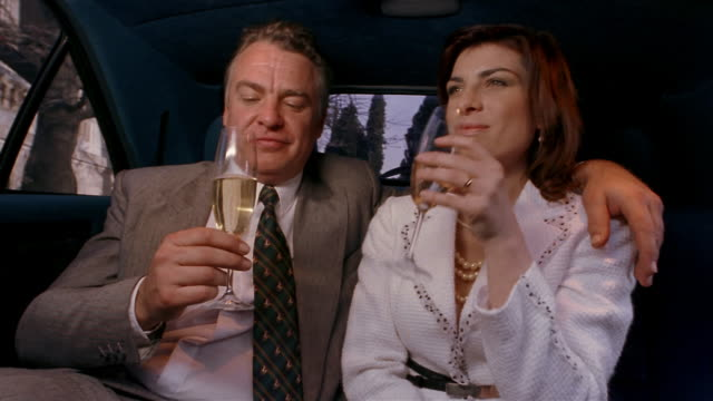 Medium shot older man and younger woman toasting + drinking champagne in limo / man kissing woman on cheek