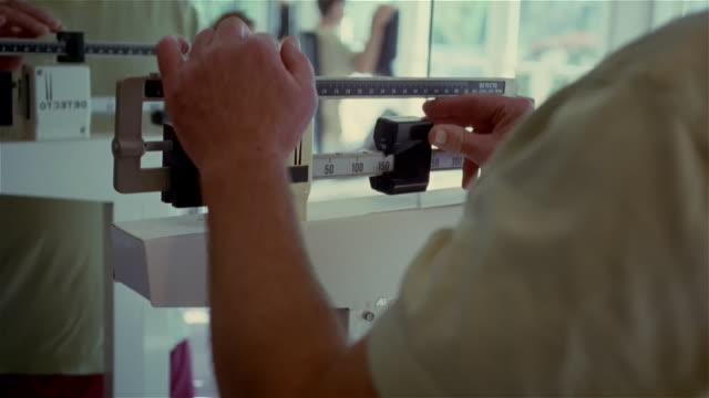 vídeos y material grabado en eventos de stock de medium shot older man weighing himself on scale in gym/ smiling at weight/ solebury, pennsylvania - régimen
