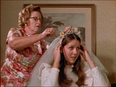vídeos de stock, filmes e b-roll de medium shot older woman with glasses adjusting bride's veil - véu