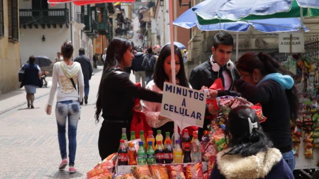 medium shot on eye level showing people buying something on a street food stand. - bogota stock videos & royalty-free footage