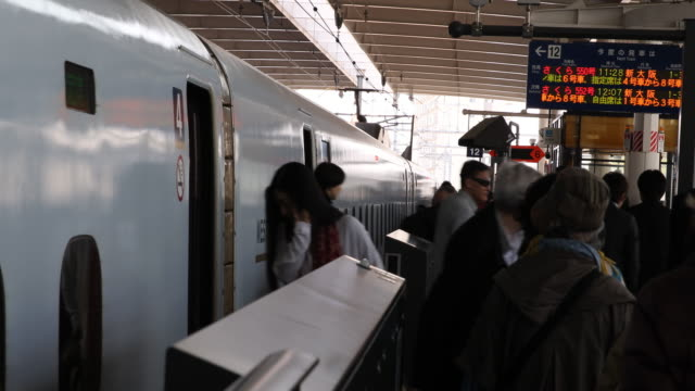 medium shot on passengers getting off and on the sakura express train the train conductor is helping a wheelchair user to get on the train - kyushu shinkansen stock videos and b-roll footage