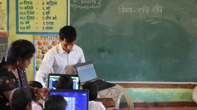 Medium shot on the teacher teaching a class learning with laptops exchanging laptops between pupils camera movement pan following the teachers...