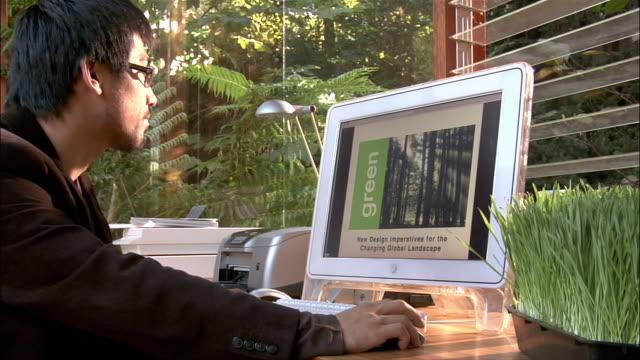 medium shot one businessman using computer in office - pc stock-videos und b-roll-filmmaterial